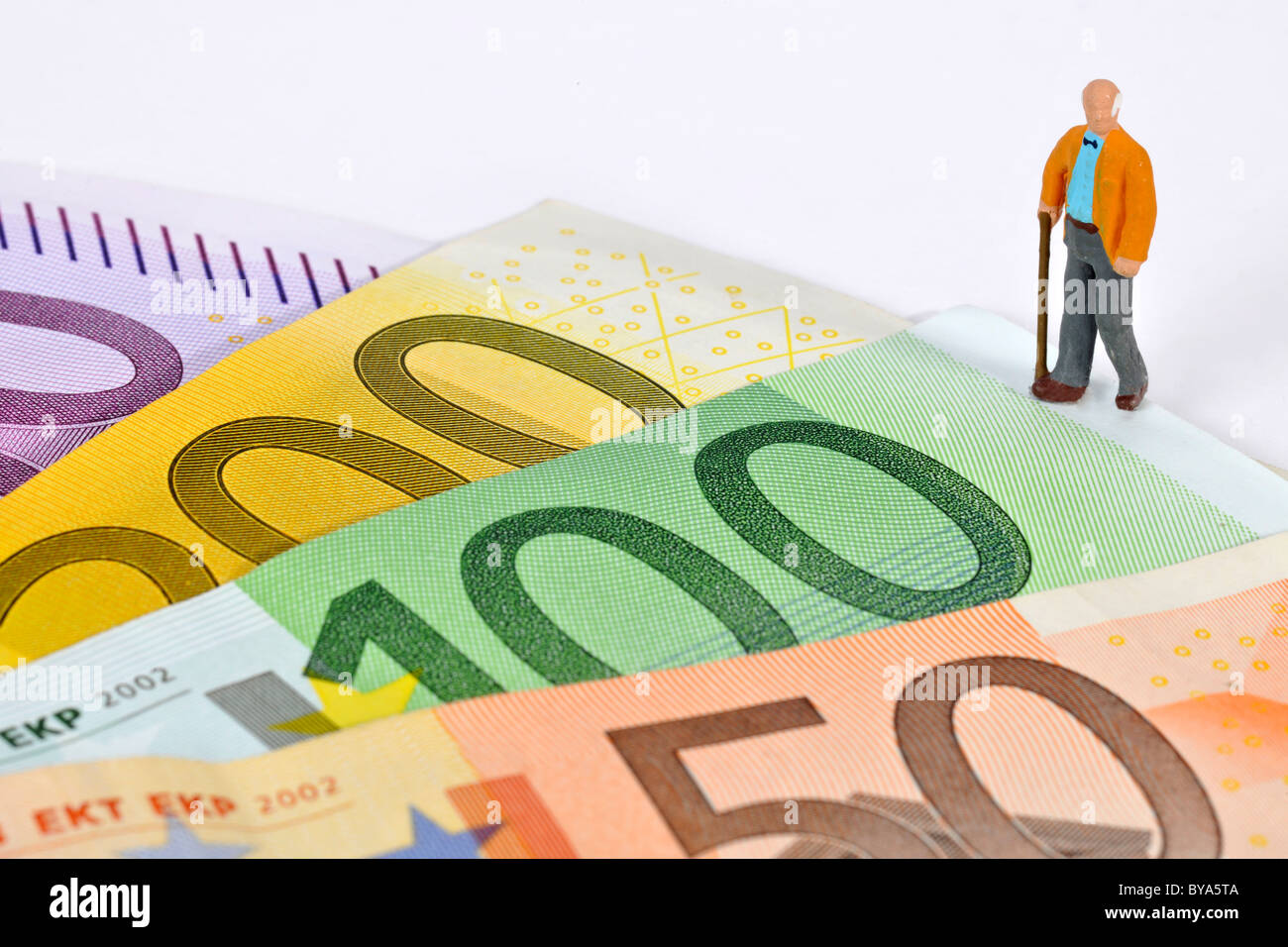 Figurine, pensioner standing on euro banknotes, symbolic image for pension plan, retirement - Stock Image