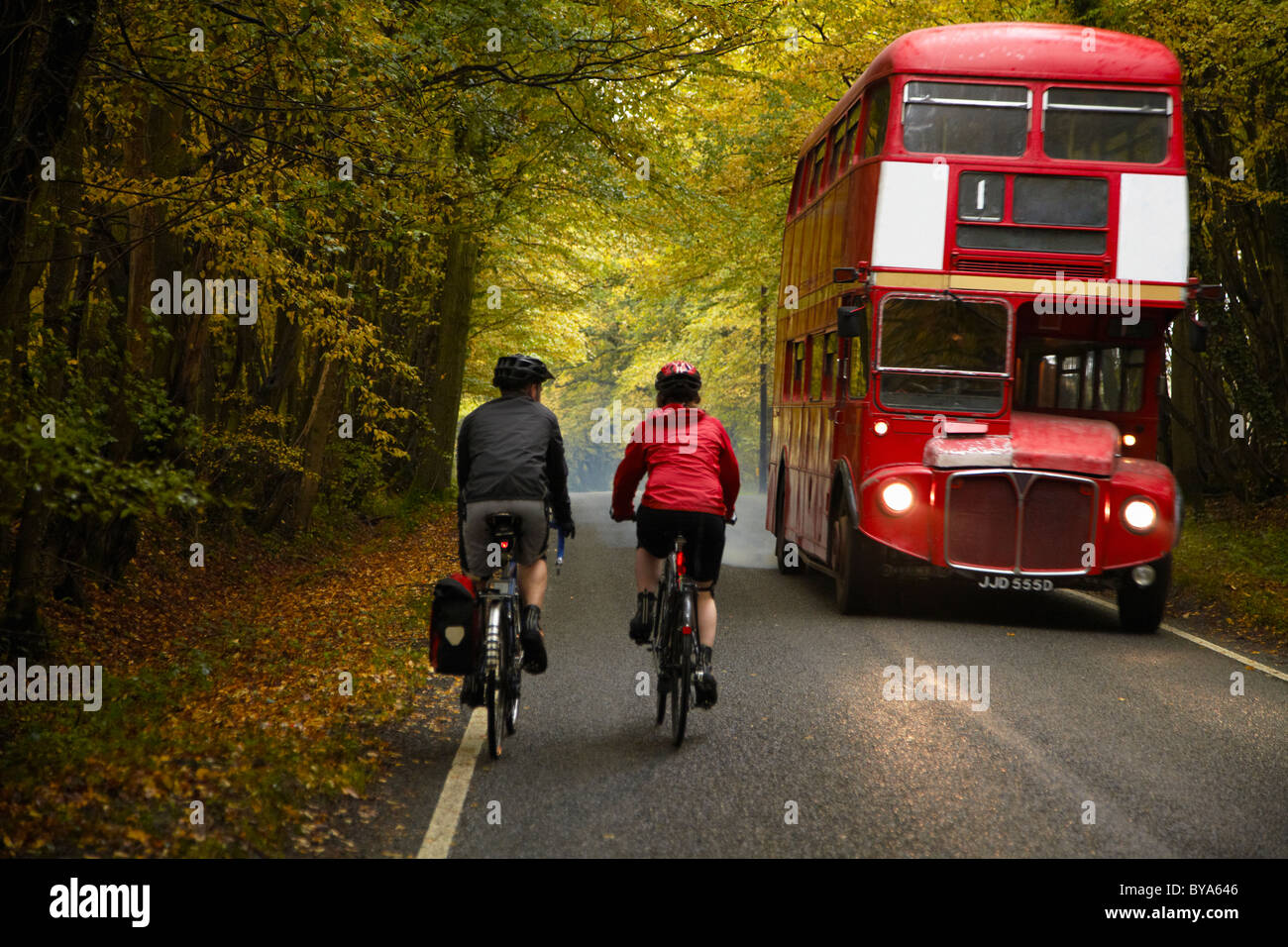 Couple cycling next to bus in country - Stock Image