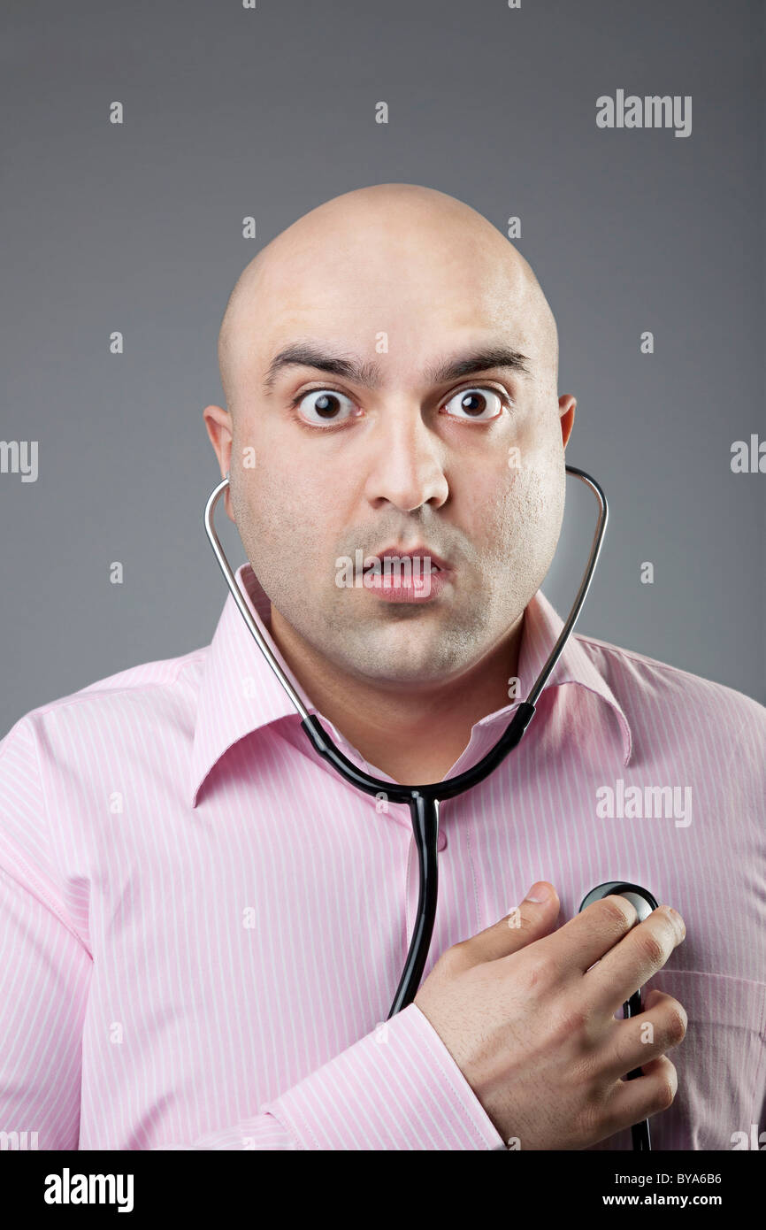 Man using a stethoscope to check his heart rate - Stock Image
