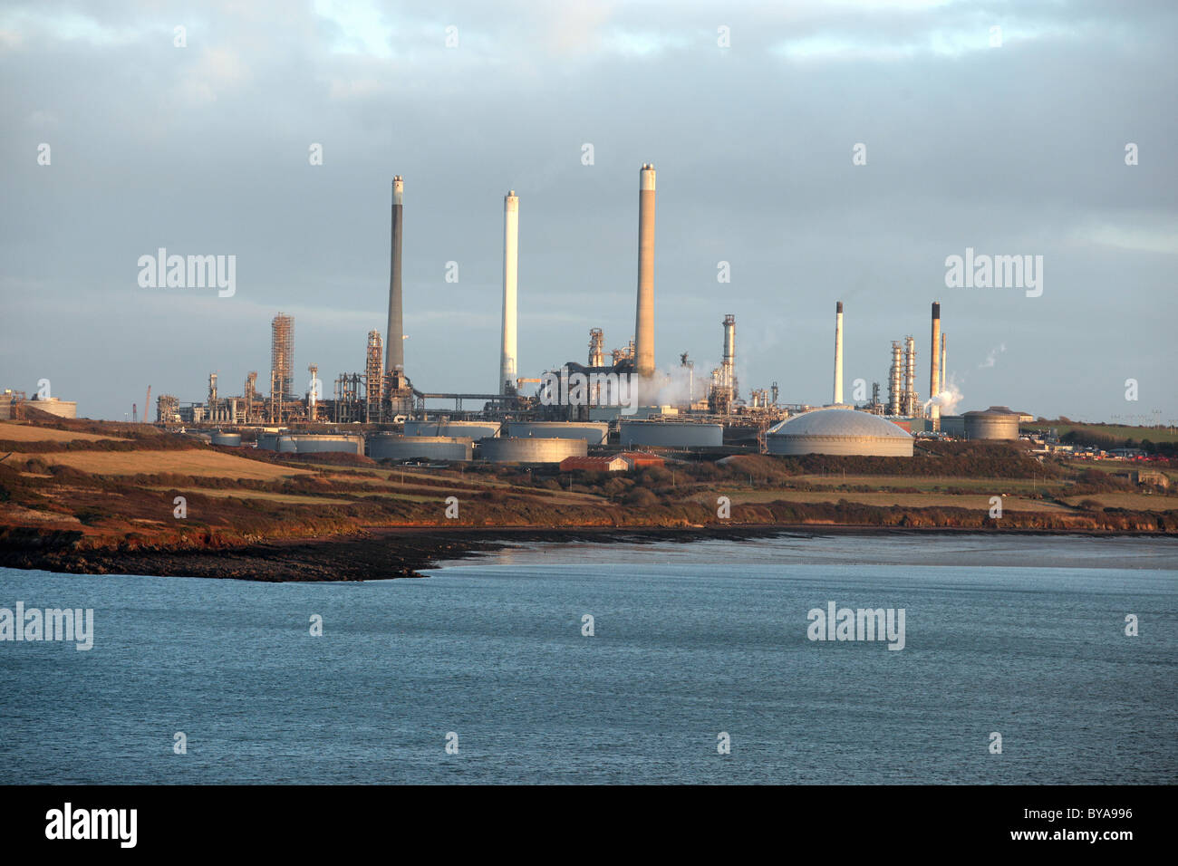 Chimneys of the Chevron refinery near Rhoscrowther as seen from Angle, Pembrokeshire - Stock Image