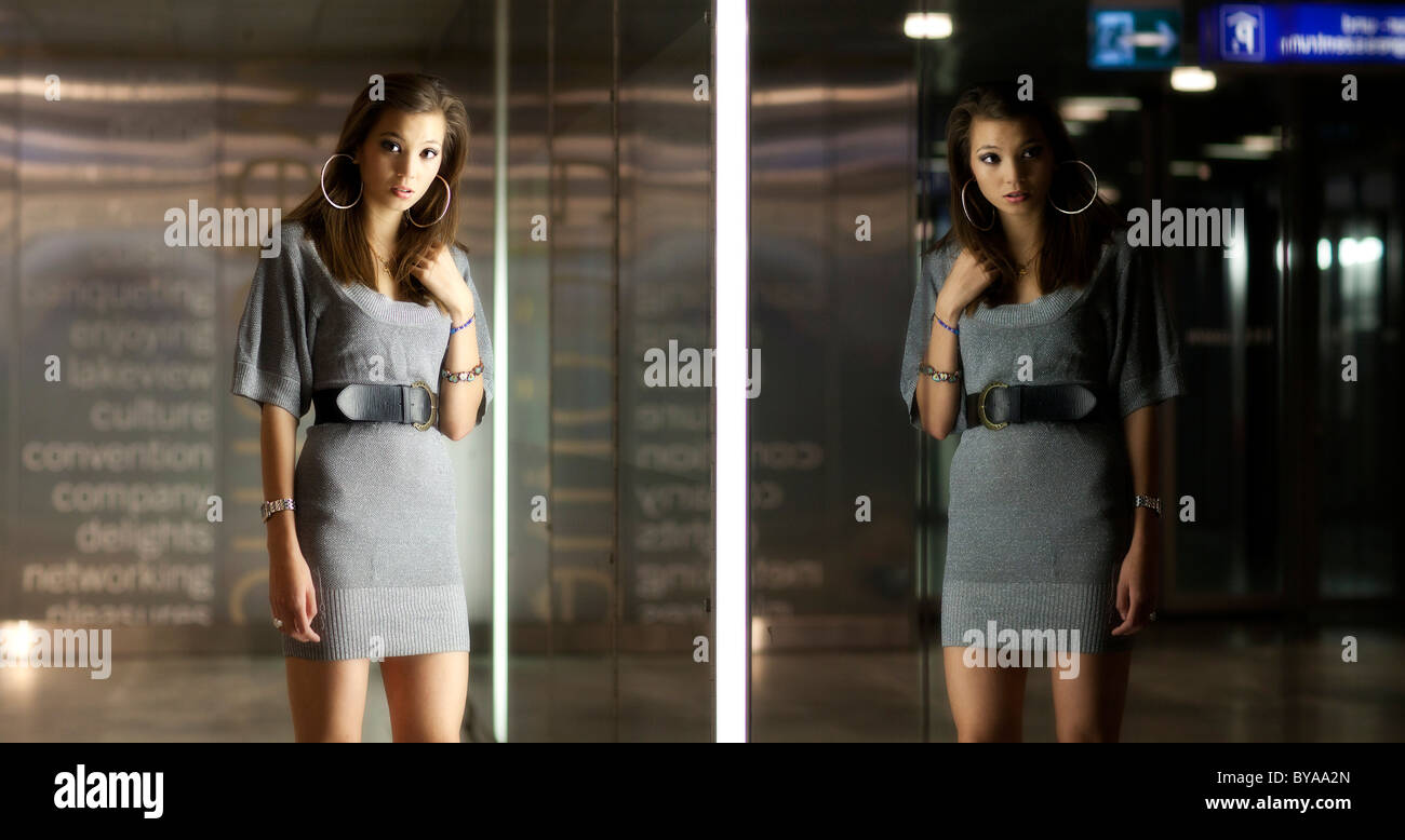 Young woman with long dark hair, posing in front of a glass mirrored wall - Stock Image