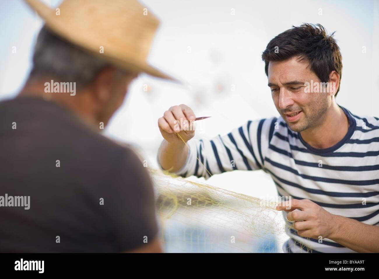Fisher preparing fishing net - Stock Image