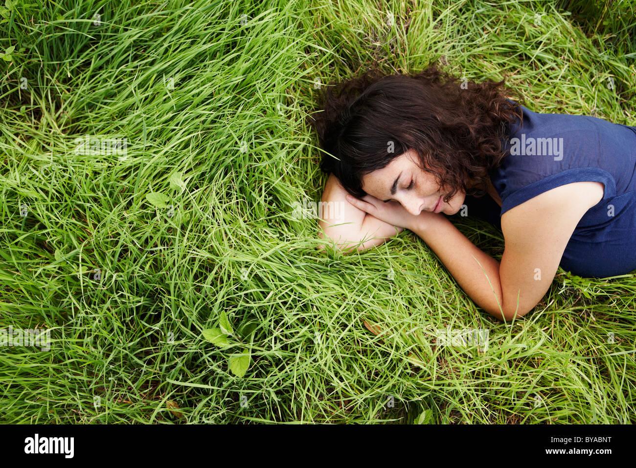 Woman sleeping in meadow - Stock Image