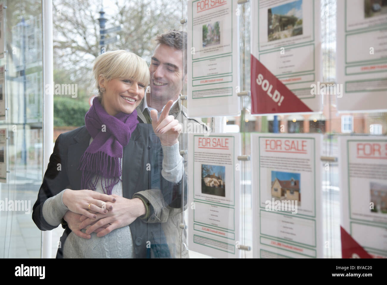 Couple looking into estate agents window - Stock Image