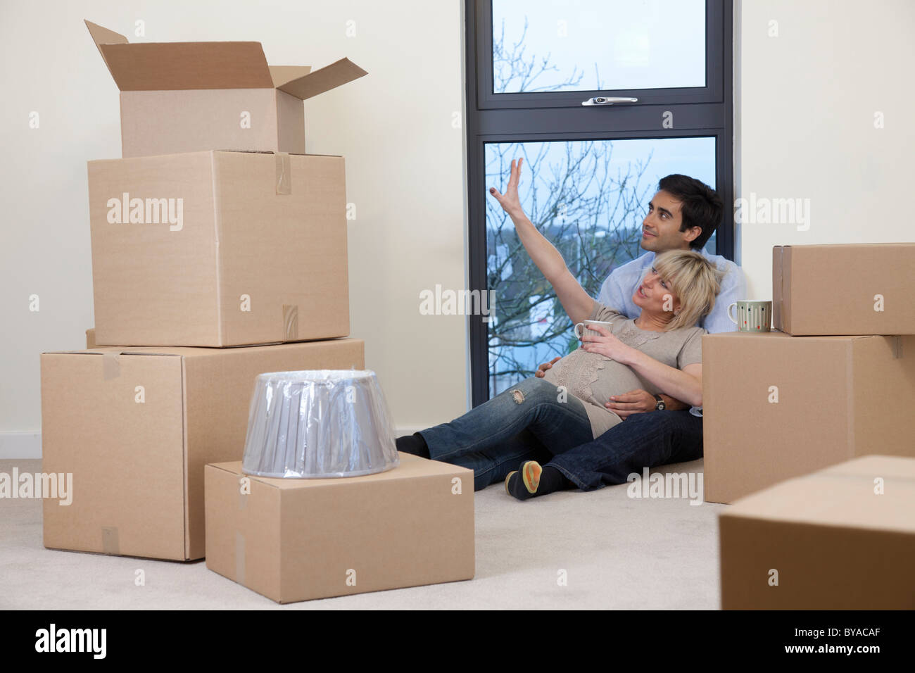 Couple sat amongst boxes in apartment - Stock Image