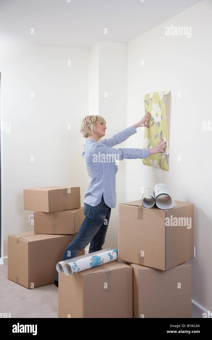 Woman looking at wallpaper samples - Stock Image