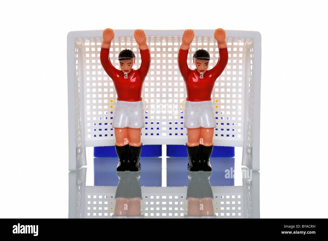 Two toy figures of goalkeepers standing in a goal, symbolic image for double security - Stock Image