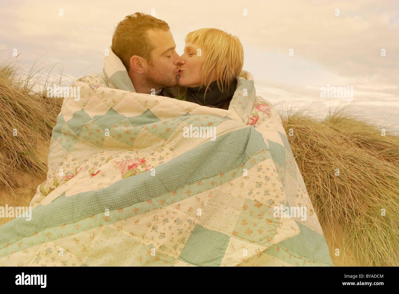 Couple Kissing Under Blanket On Beach