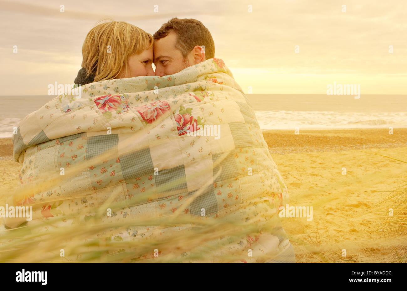 Couple Cuddling Under Blanket On Beach