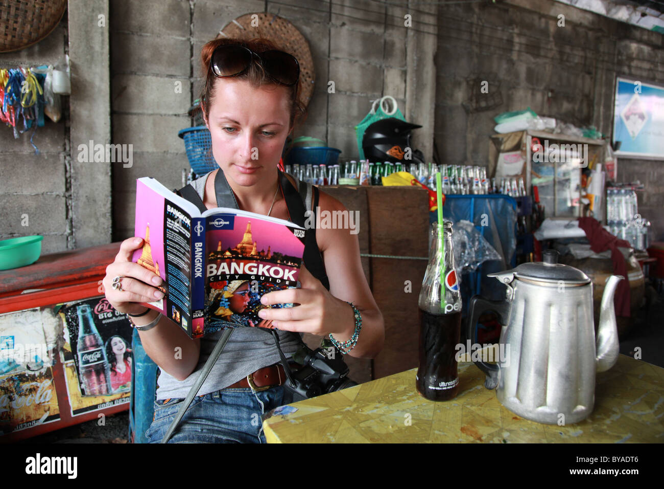 Female tourist reading Bangkok Guide book, in Thailand - Stock Image