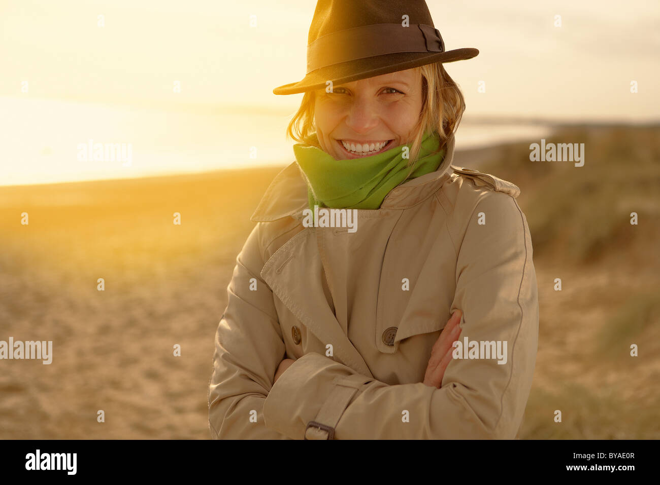 Young woman on beach in hat and raincoat Stock Photo