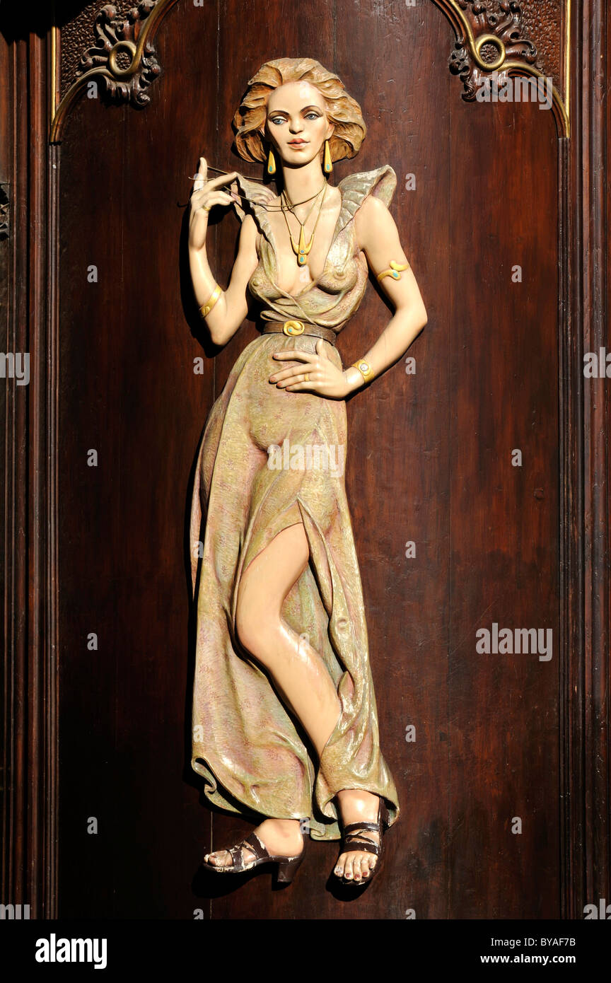 Art Nouveau house emblem of a lascivious woman, wood relief on the facade of the Caffè per Lei Cafe, historic district,Stock Photo
