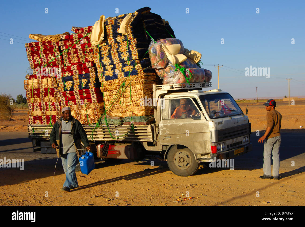 An overcharged pickup carrying colourful matrasses, Al Awaynat, Libya, North Africa - Stock Image