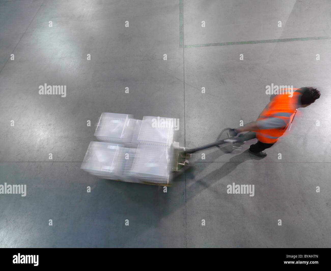 Worker pulls pallet truck - Stock Image