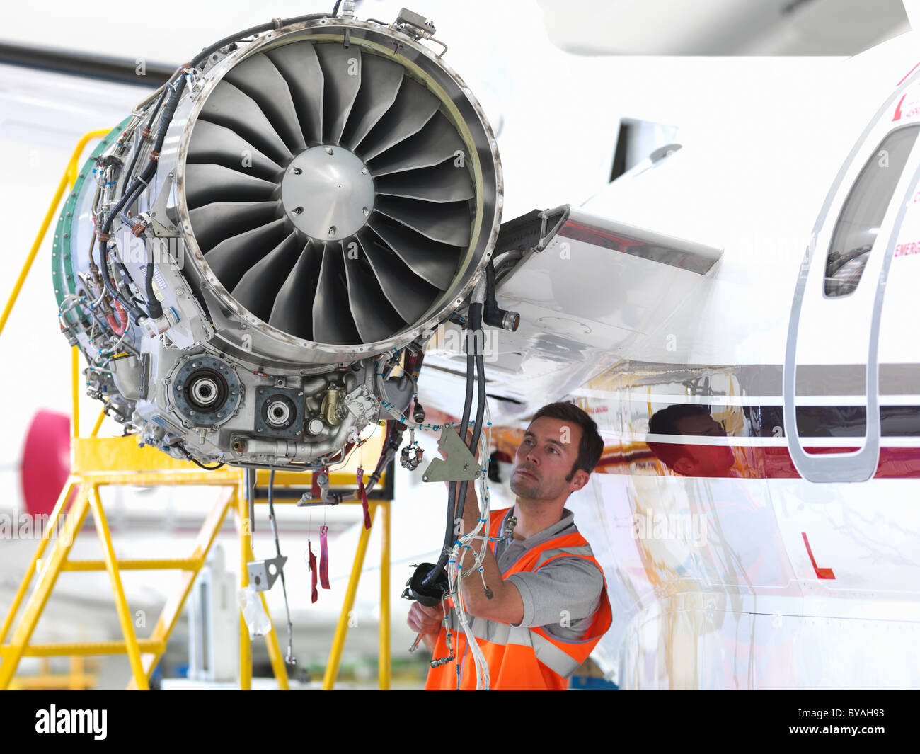 Engineer inspects jet engine - Stock Image