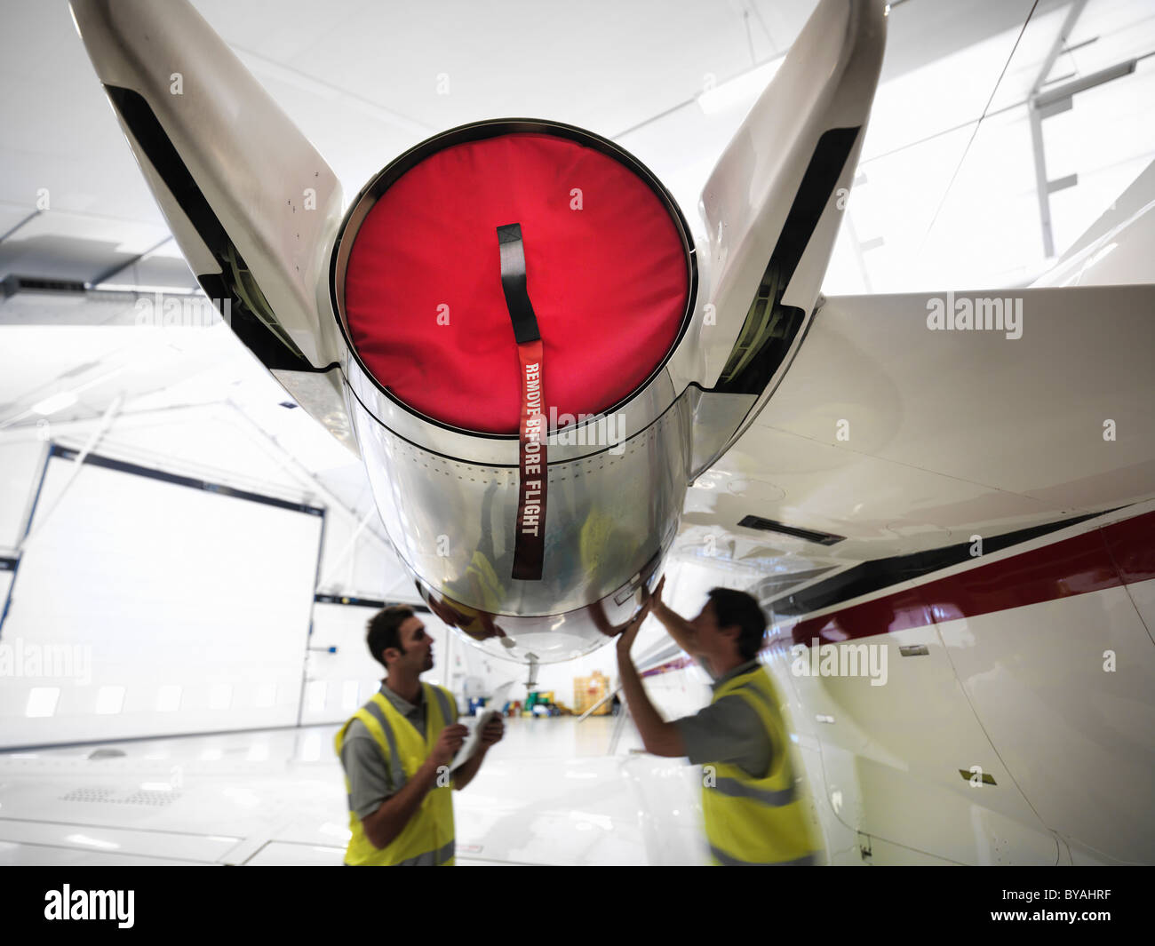 Engineers working on jet aircraft - Stock Image