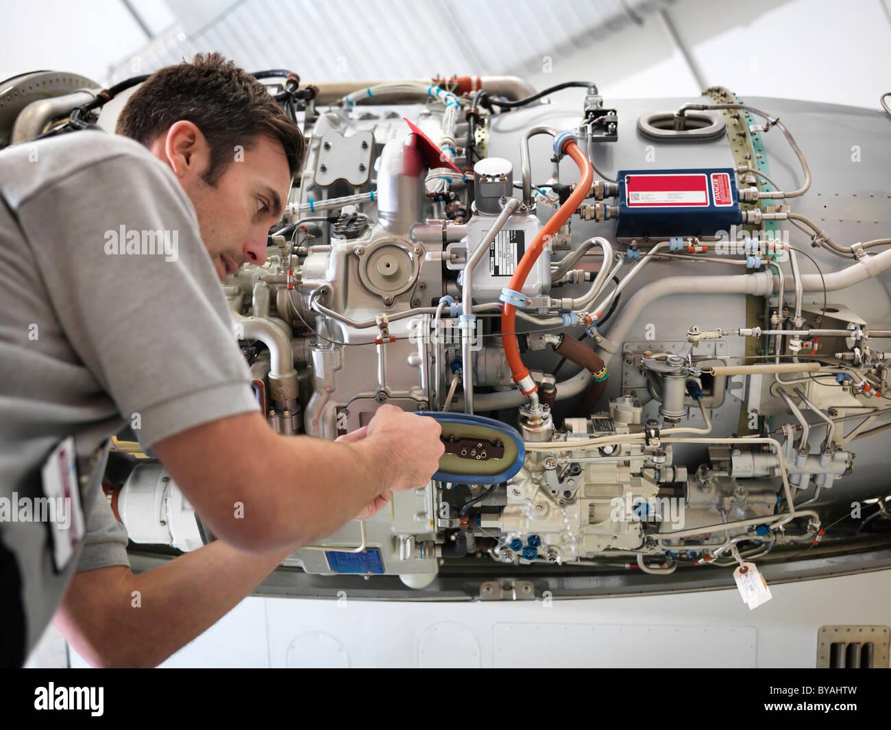 Engineer works on jet engine - Stock Image