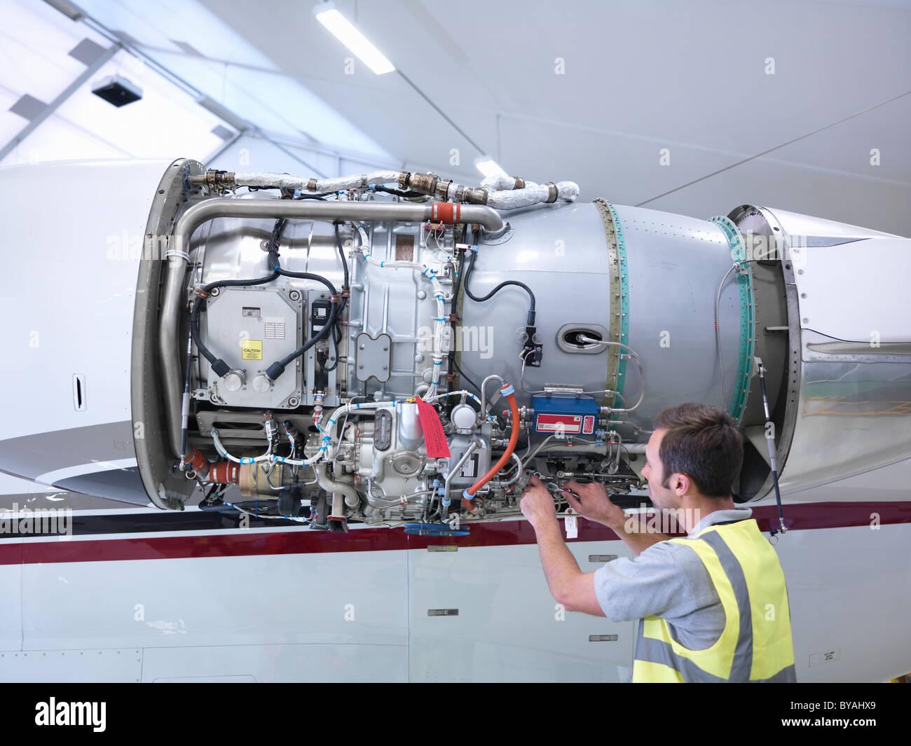Engineer working on jet engine - Stock Image