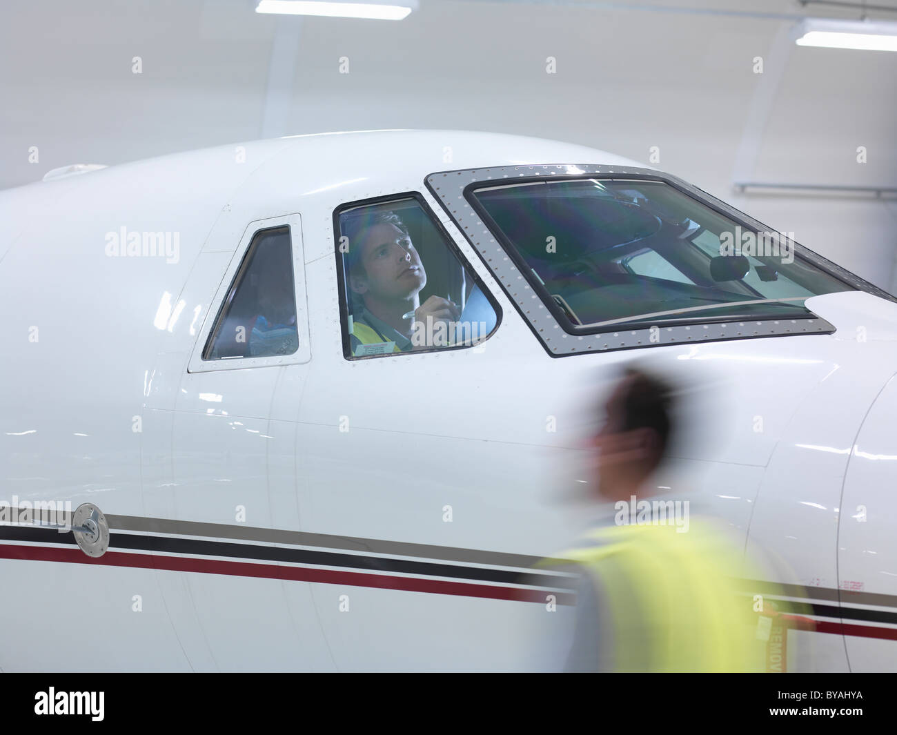 Engineer inspects jet cockpit - Stock Image