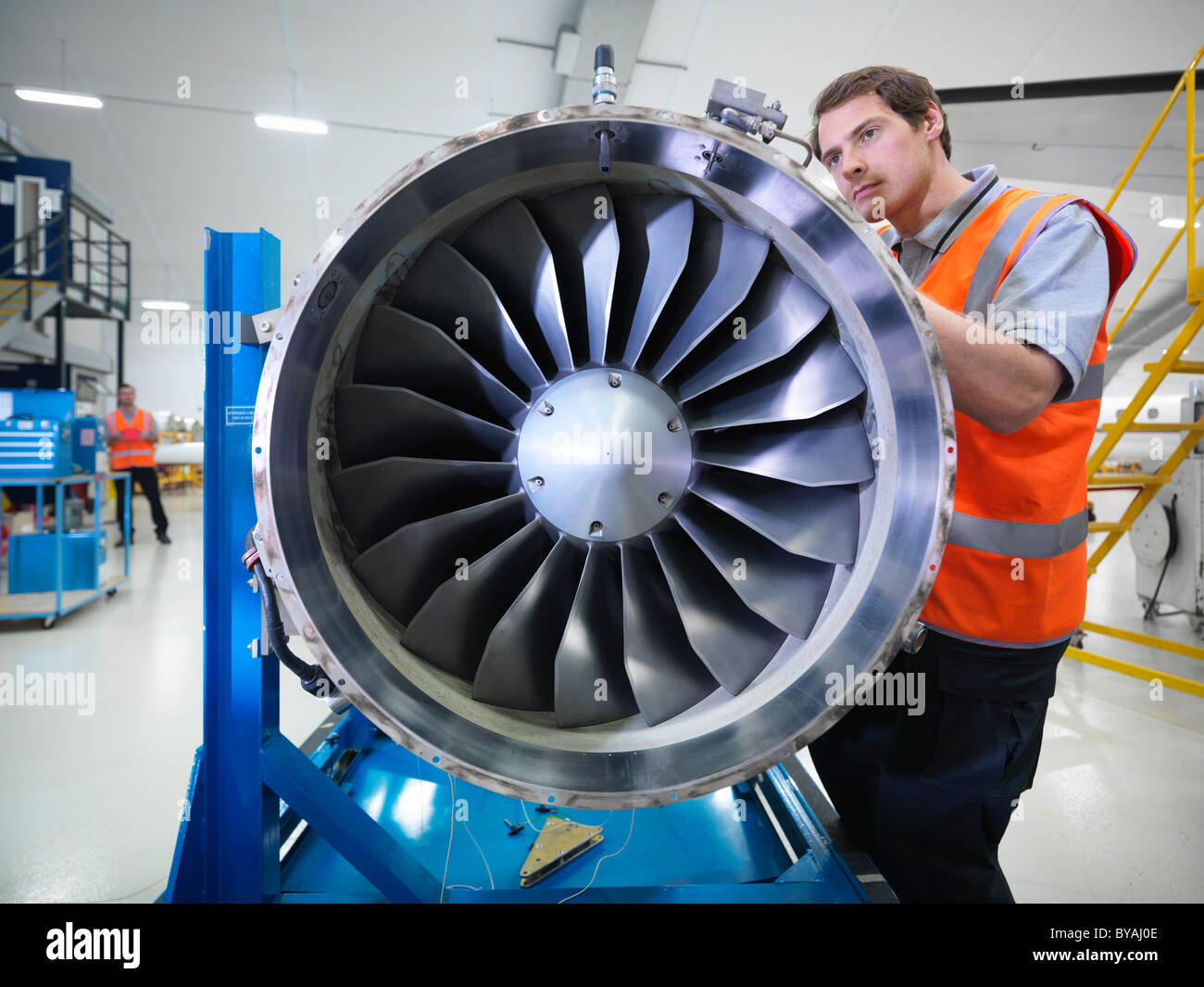 Engineer works on jet engine - Stock Image