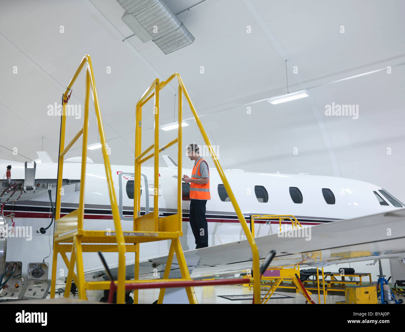 Engineer inspects jet aircraft - Stock Image