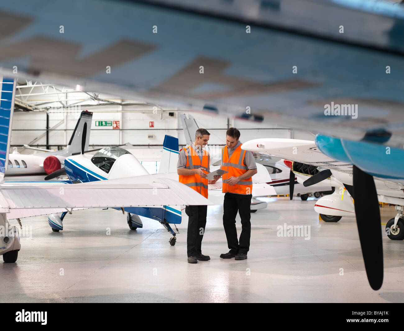 Engineers inspect turbo-prop aircraft - Stock Image