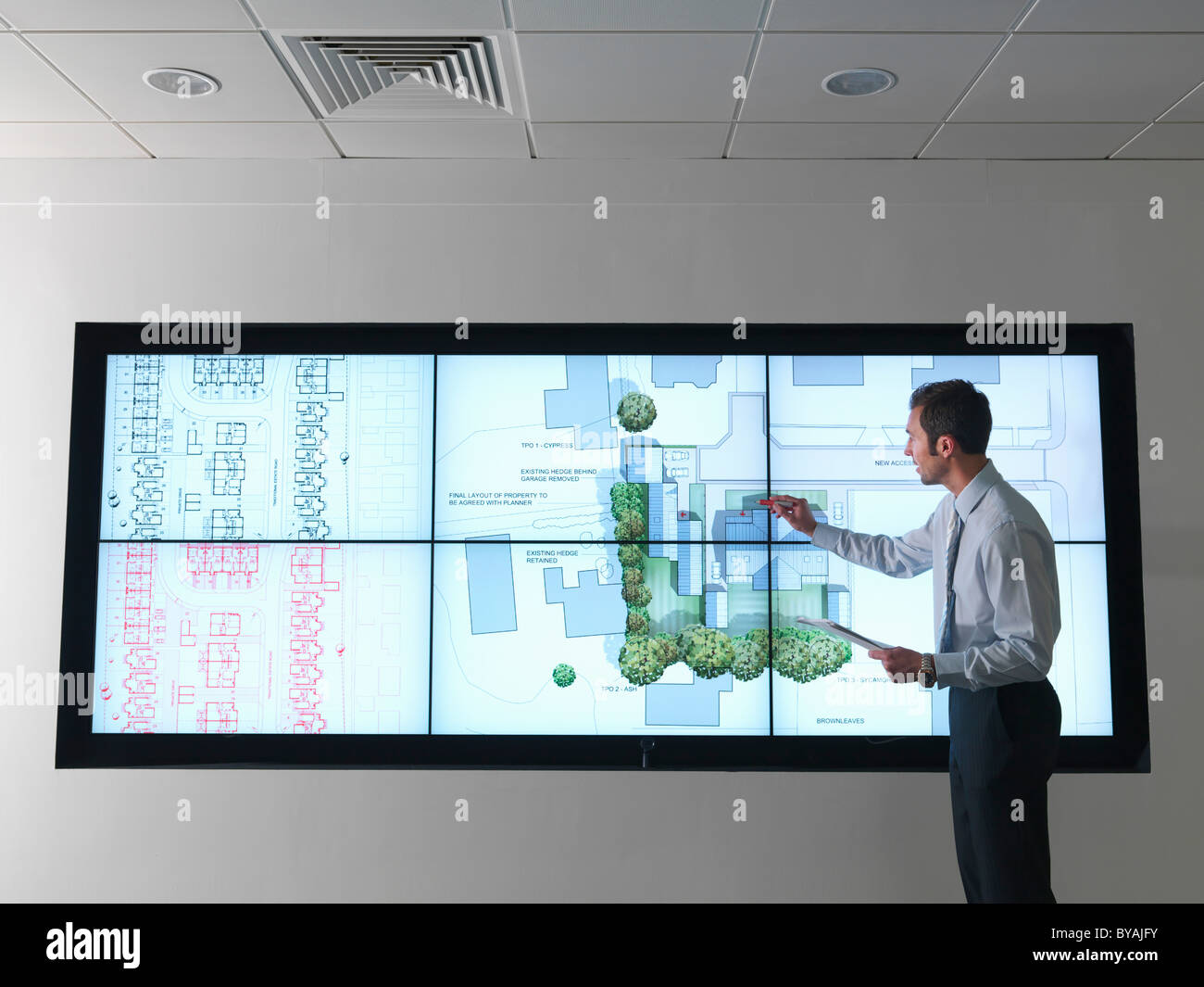 Architect works at plans on screen - Stock Image