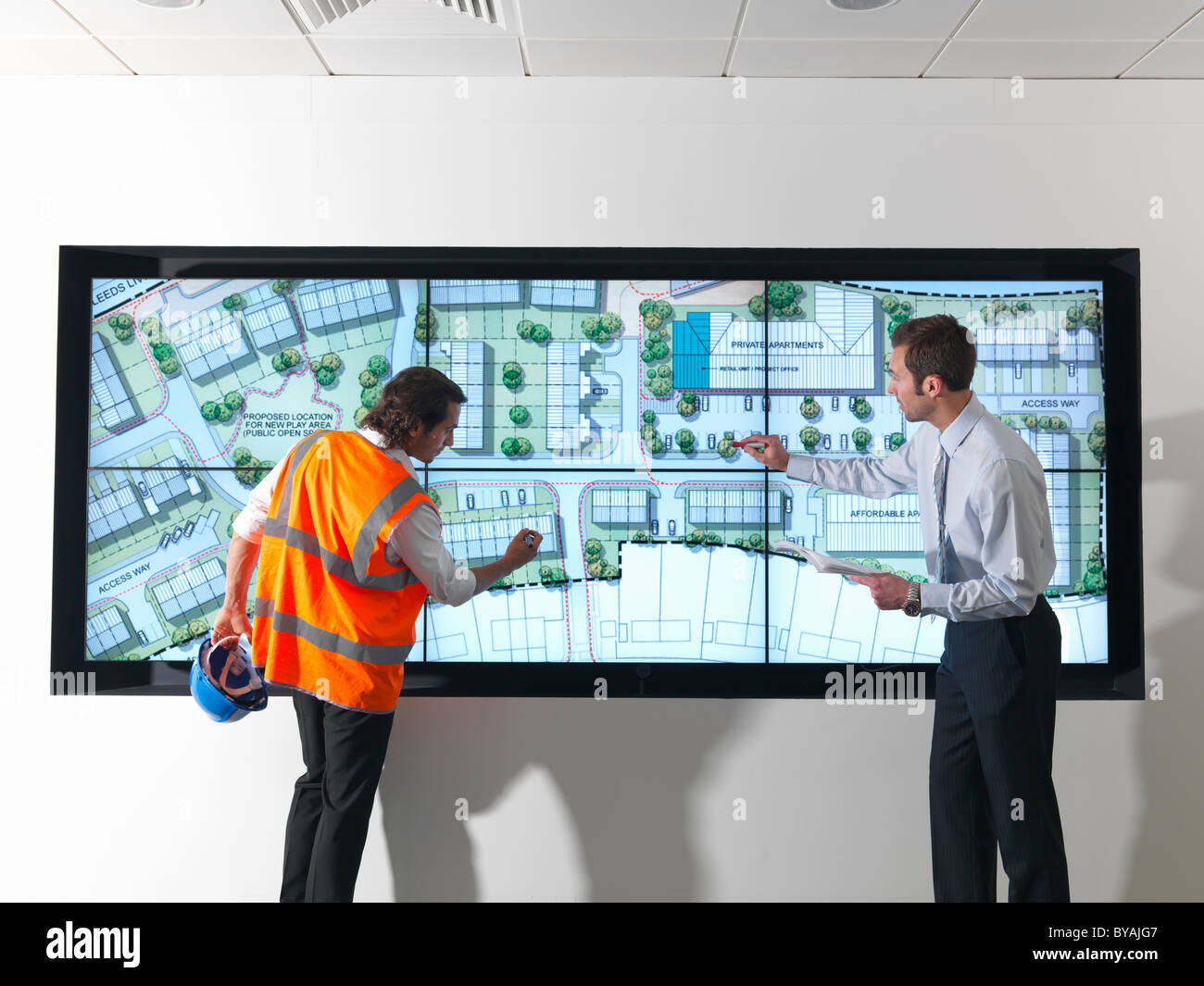 Town planners look at plans on screen - Stock Image