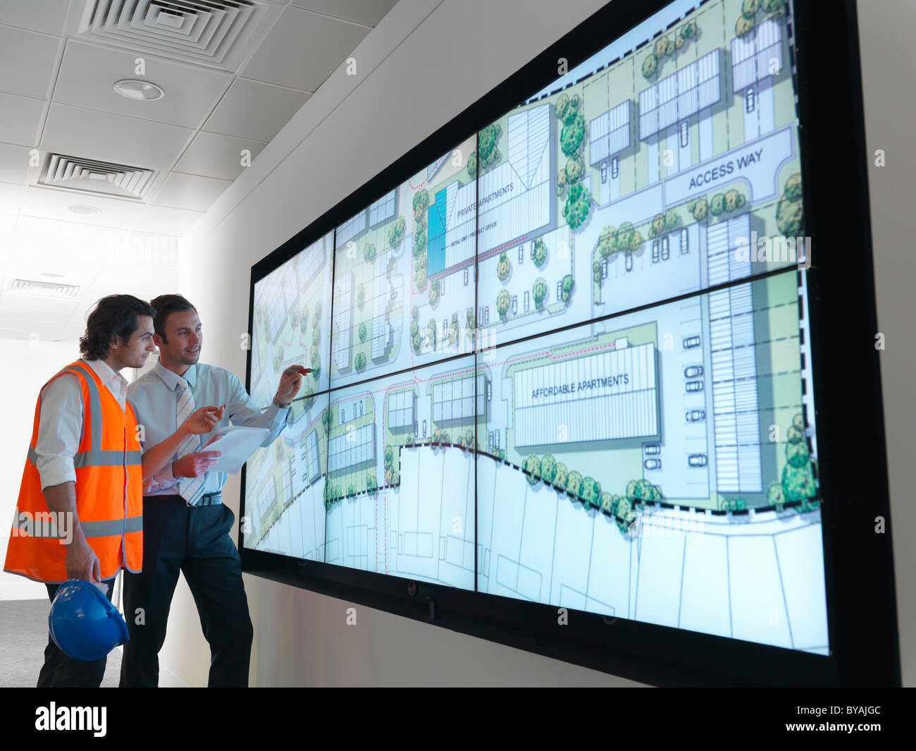 Town planners work at plans on screen - Stock Image