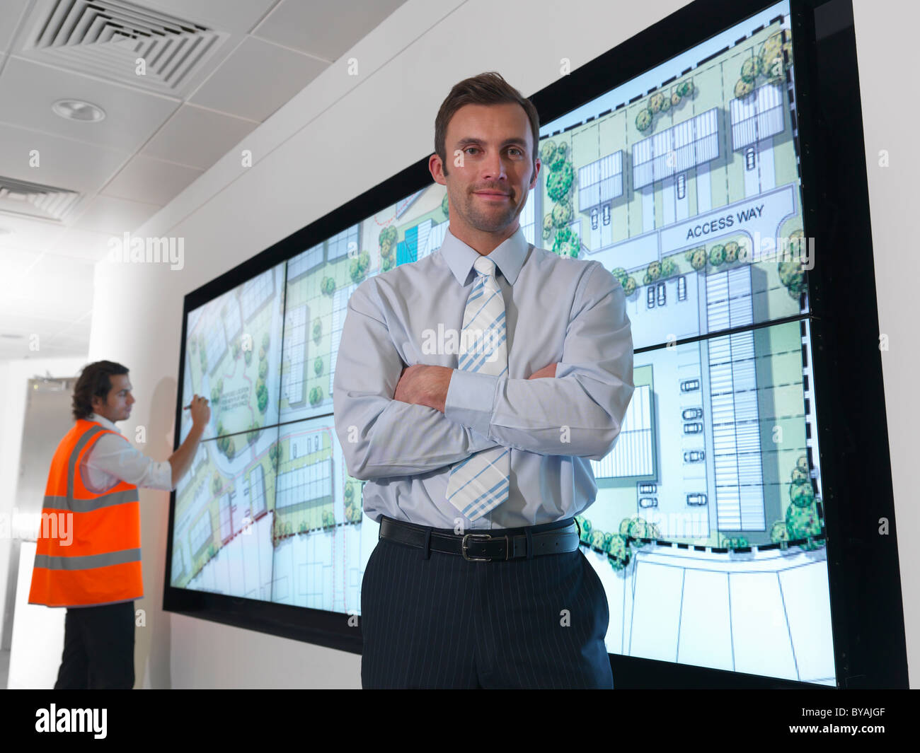 Architects with plans on screen - Stock Image