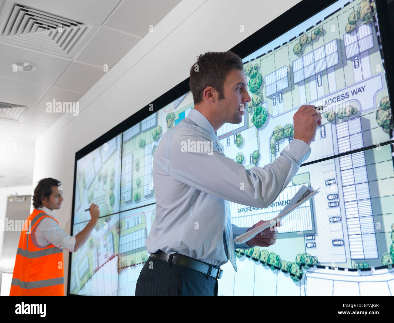 Town planners with plans on screen - Stock Image