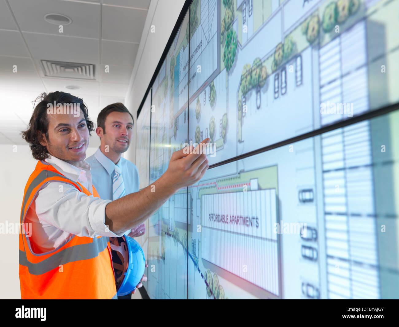 Architects work with plans on screen - Stock Image