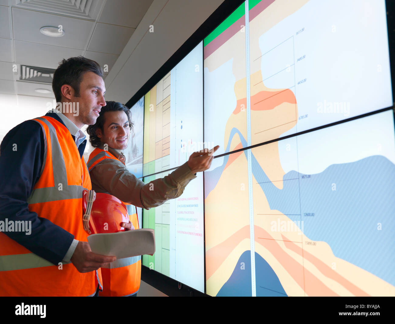 Oil workers with geology screen - Stock Image