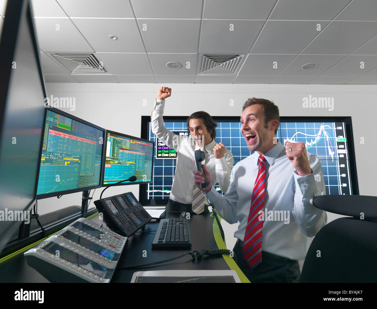 Successful financial trader and screens - Stock Image