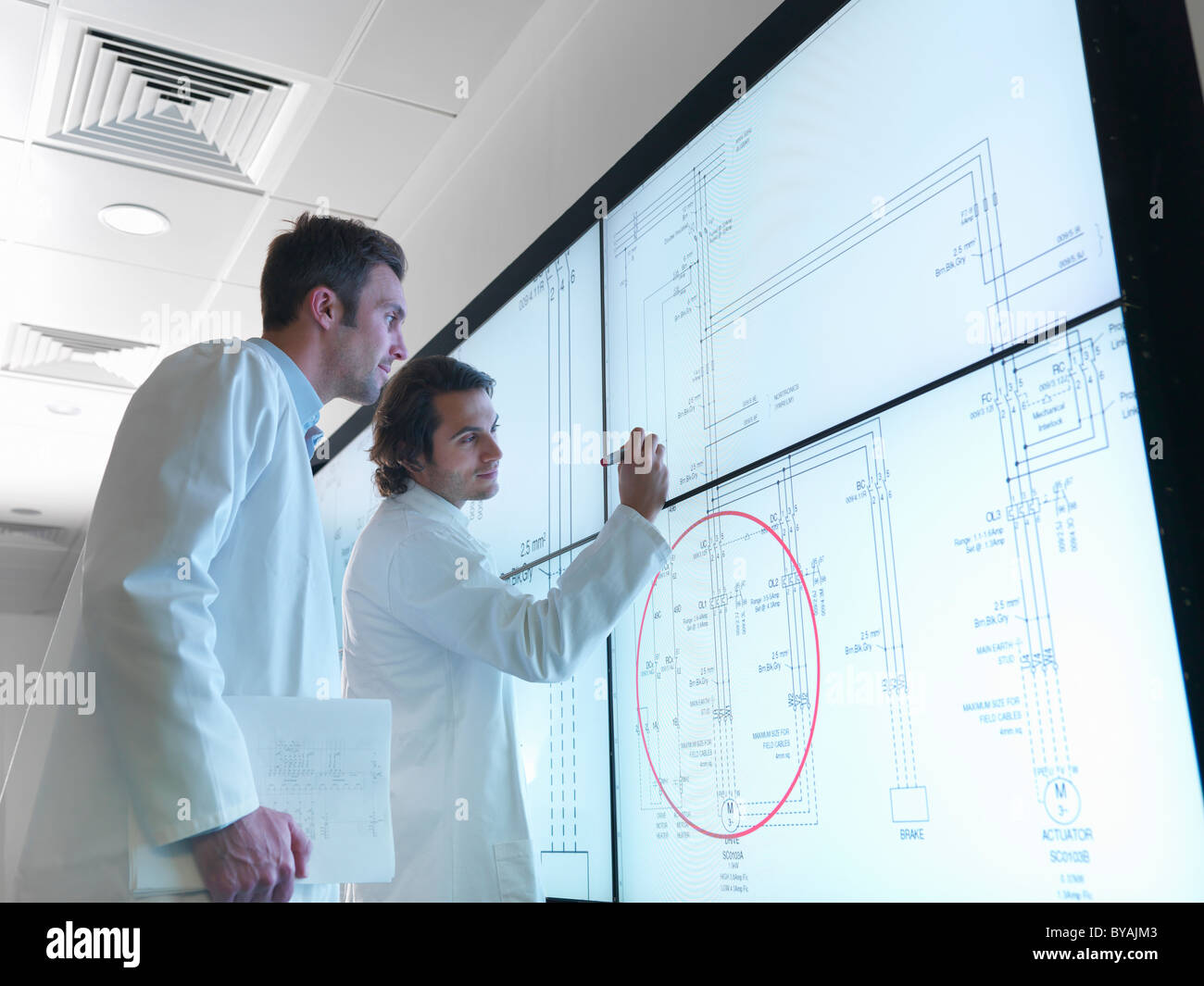 Scientists with diagrams on screen - Stock Image