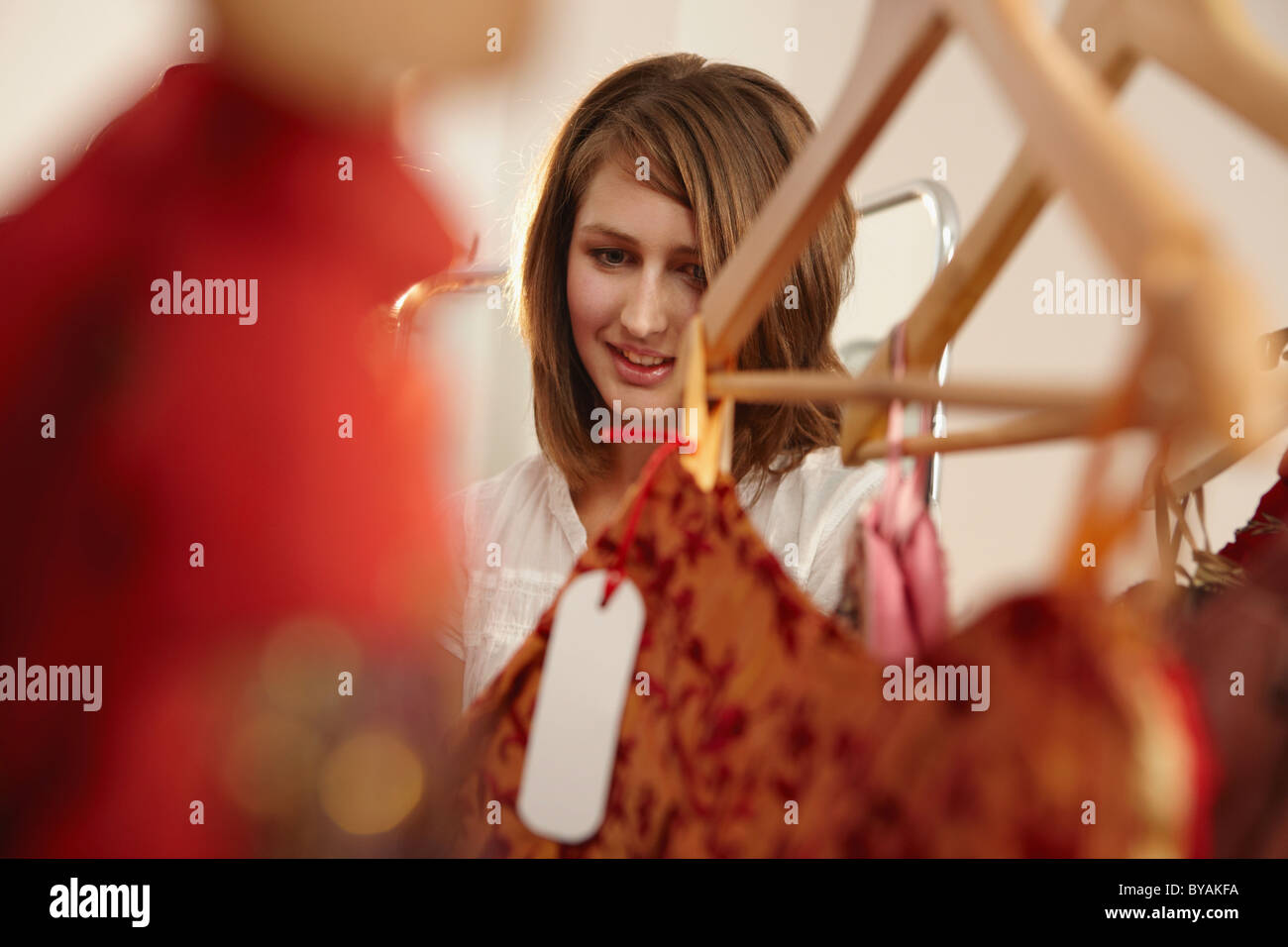 Young lady fascinated in fashion store - Stock Image
