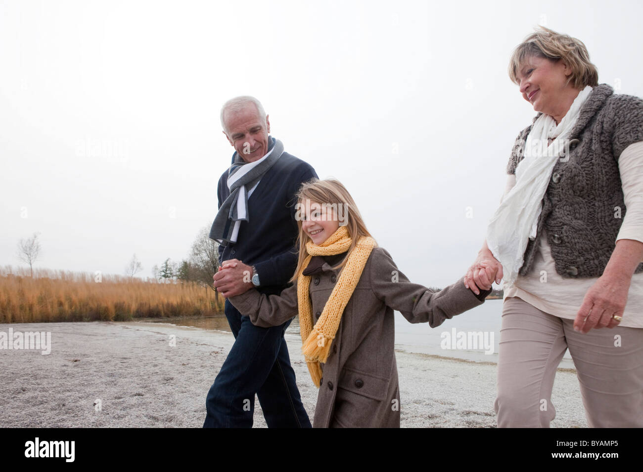 Grandparents and girl walking by lake - Stock Image