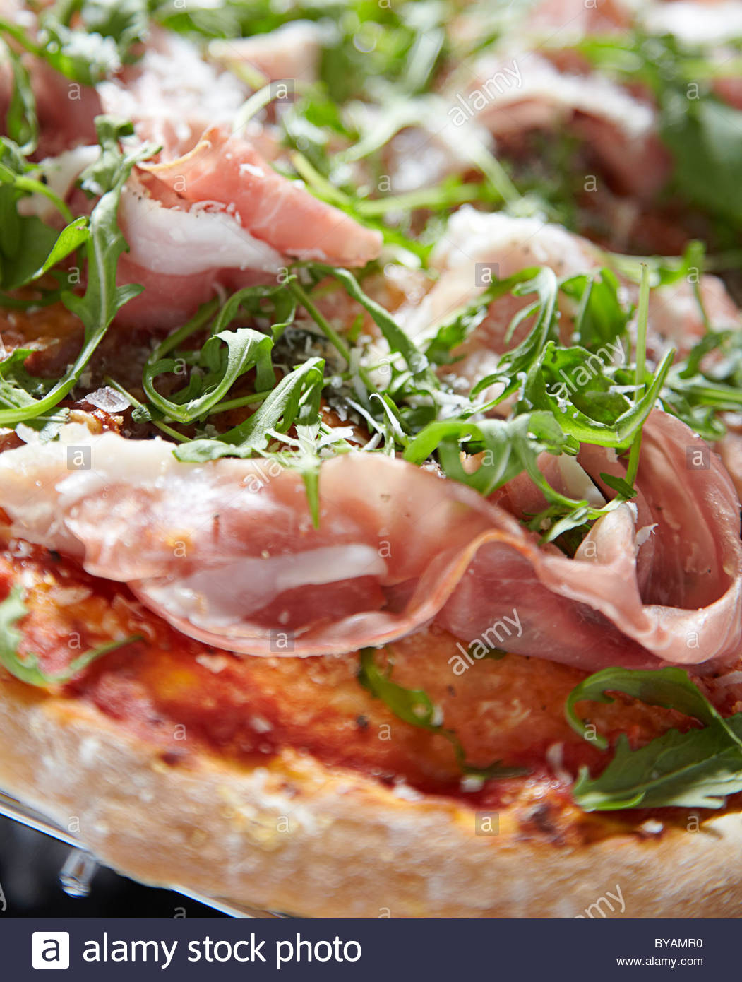 Thin crust Pizza with parma ham and rocket salad and cheese tomato base - Stock Image