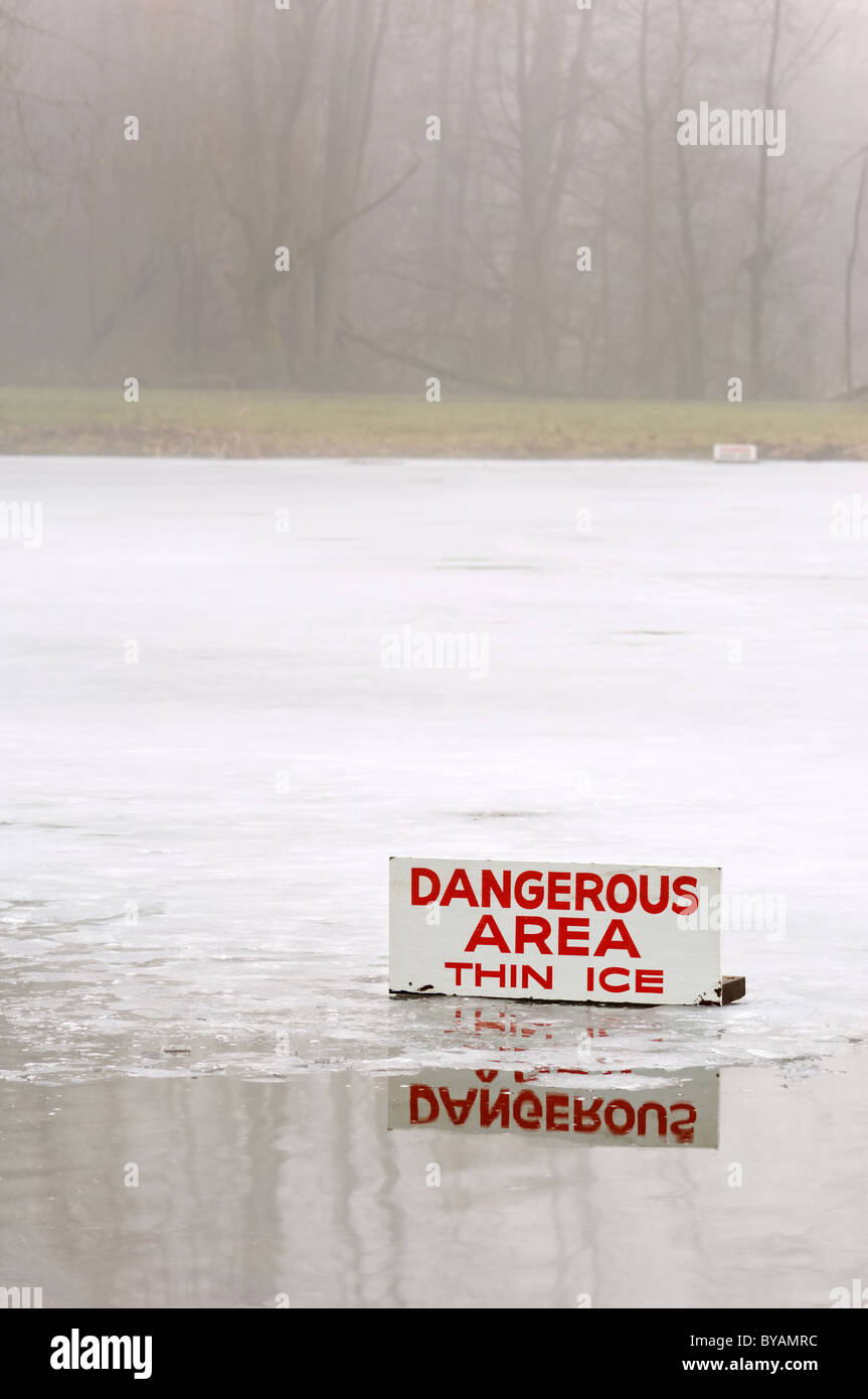 A pond covered in a thin layer of ice with some open water, and a sign signifying the danger during a foggy day. - Stock Image