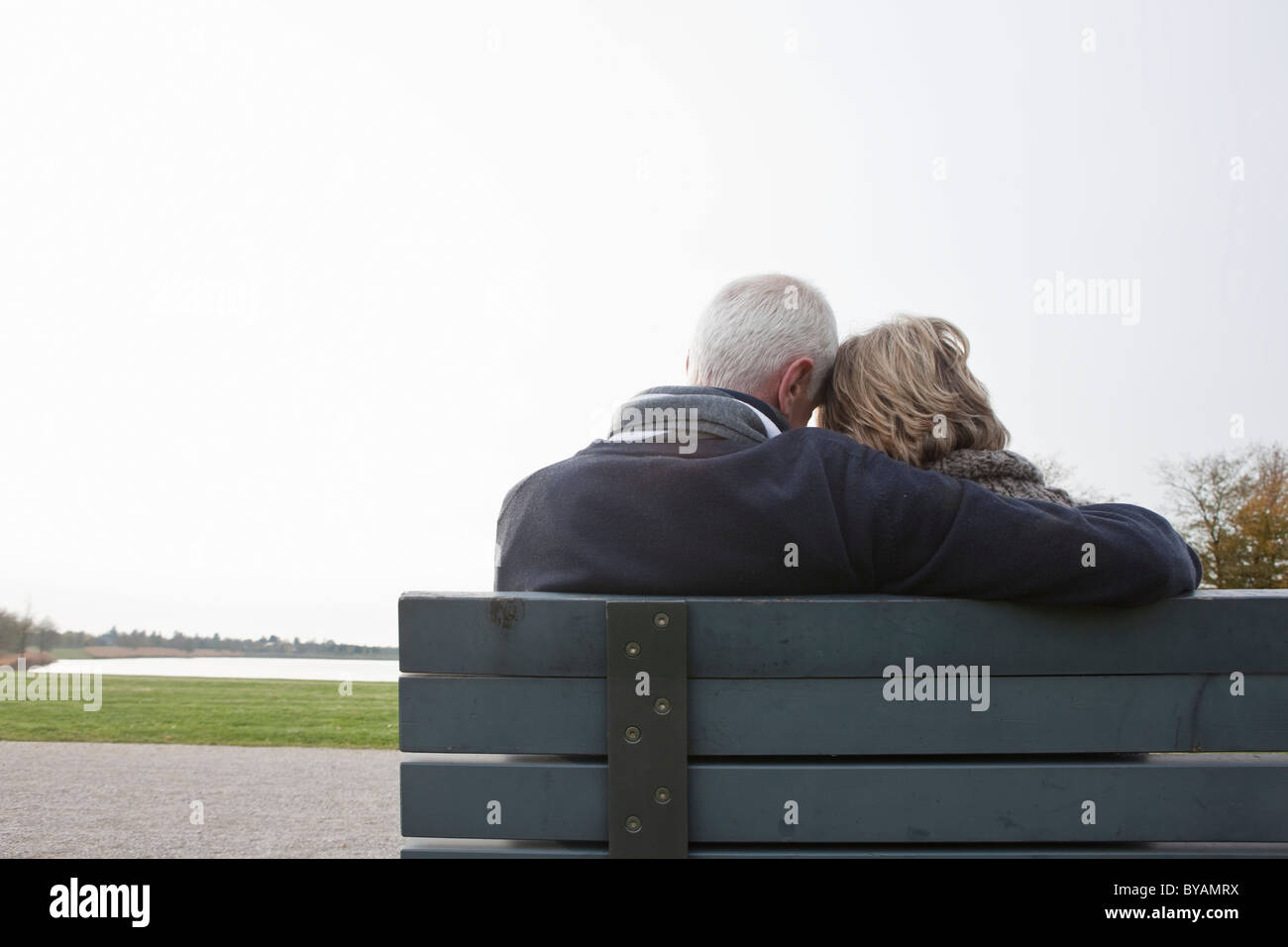 Senior couple sitting on bench in park - Stock Image