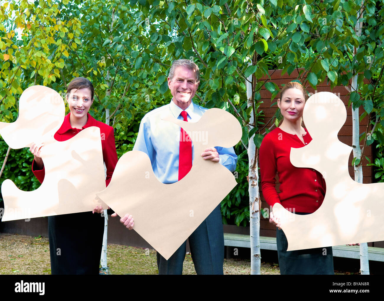 Business team hold jigsaw pieces - Stock Image