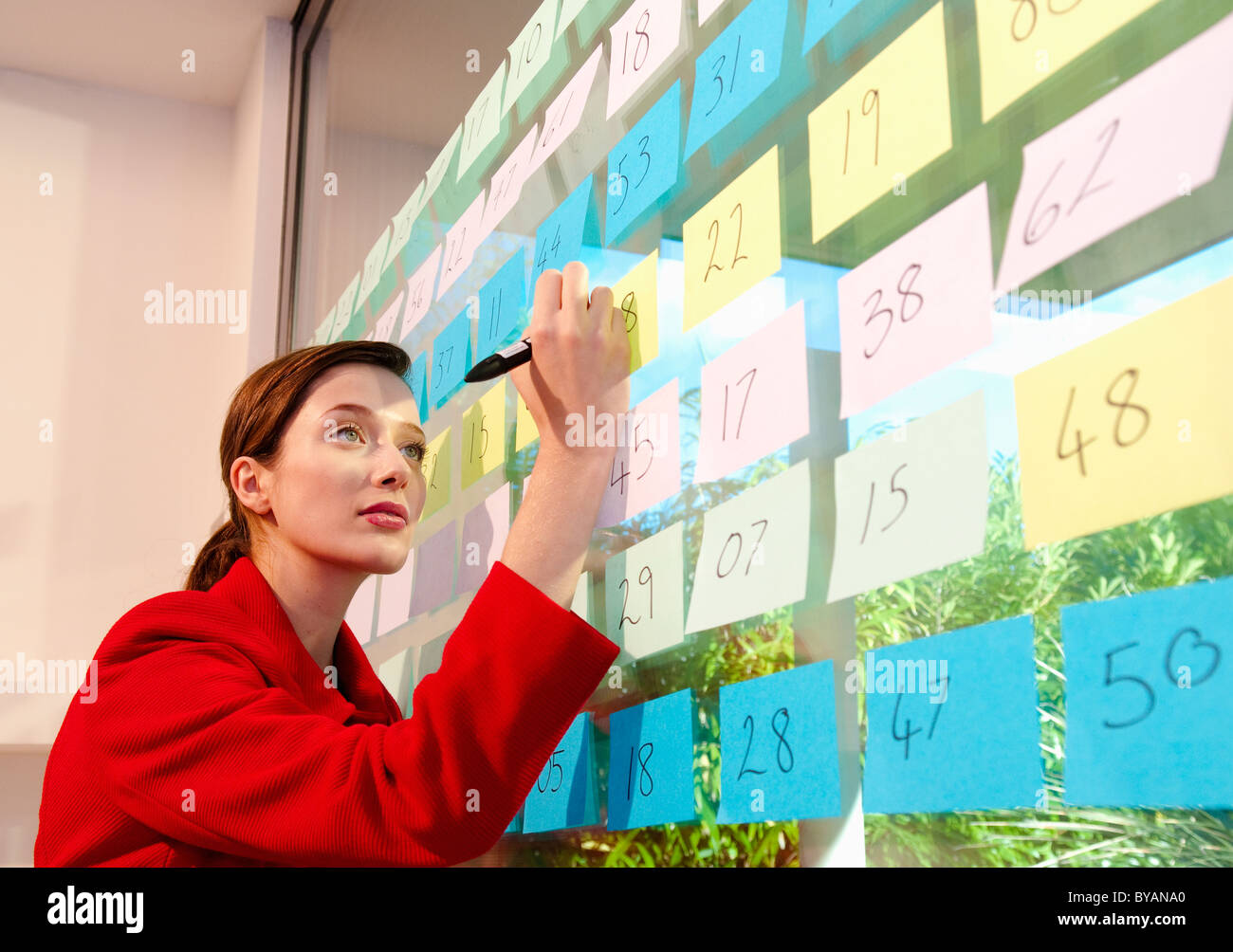 Woman writes on sticky labels - Stock Image