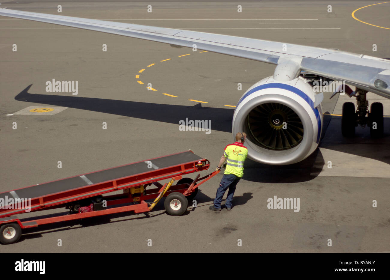 Baggage handler for Virgin Blue at the Sydney Domestic Airport - Stock Image