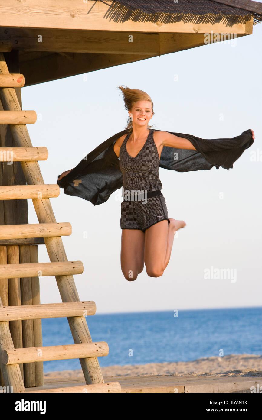 Beautiful girl jumping beach - Stock Image