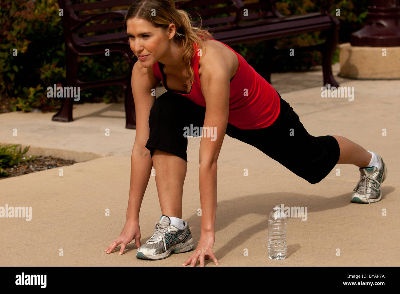 Outdoor spring training exercise in city park showing beautiful young blond Caucasian woman enjoying working out Stock Photo
