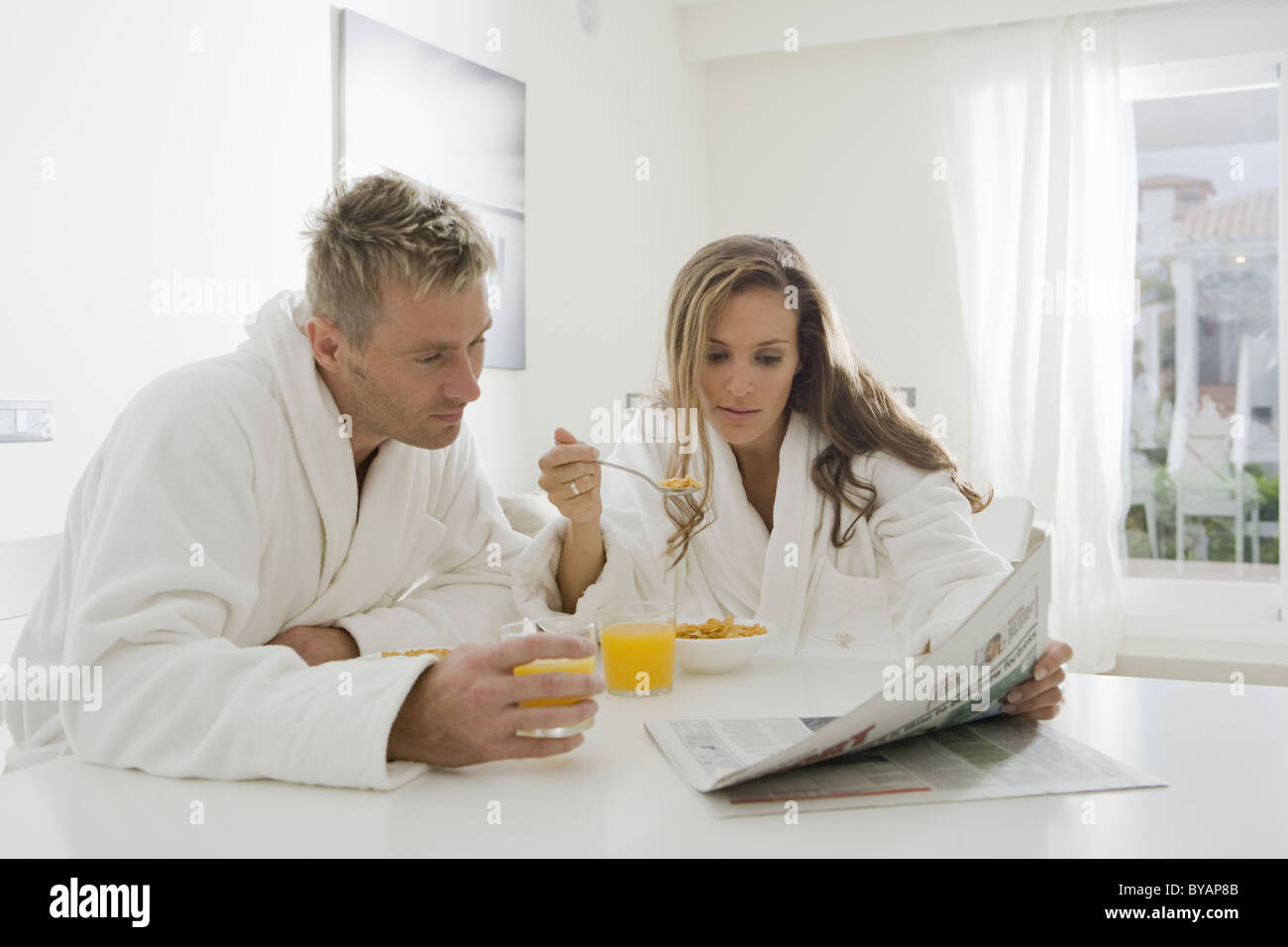 Young couple reading paper at breakfast Stock Photo