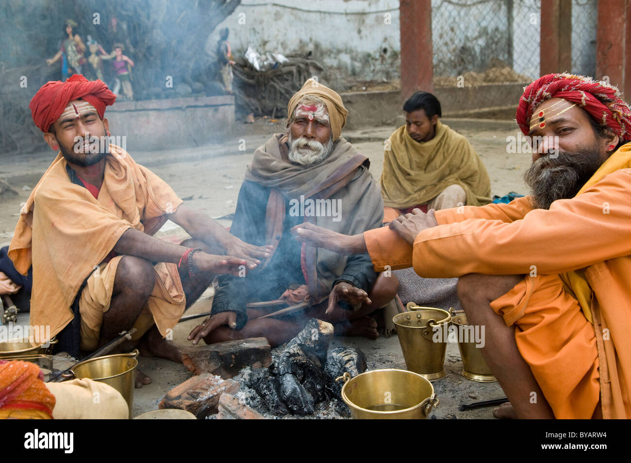 Early morning scene. Sadhus by the campfire. - Stock Image