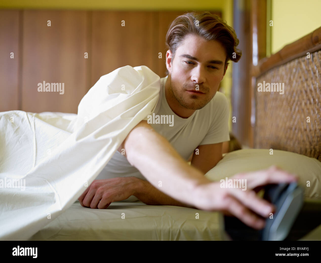 caucasian adult man in bed snoozing alarm clock and waking up. Horizontal shape, waist up, front view - Stock Image