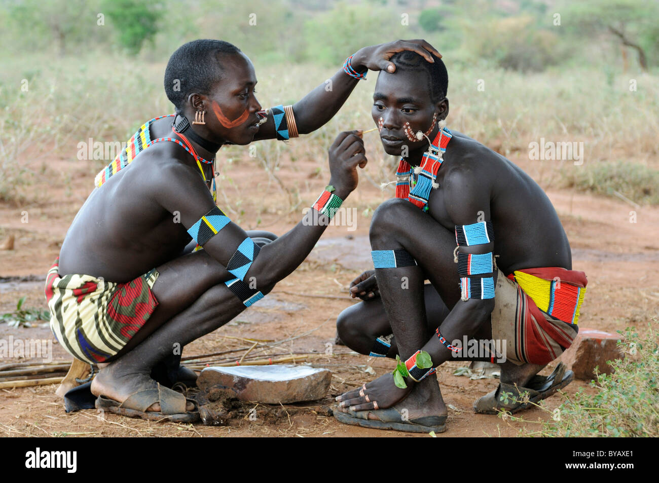 Men from the Hamar tribe painting each other for the initiation ritual 'leap over the cattle', southern - Stock Image
