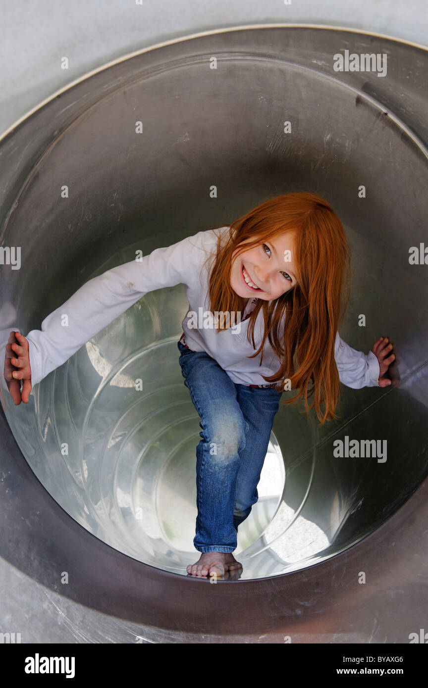 Girls playing in a tubular slippery dip at a playground - Stock Image